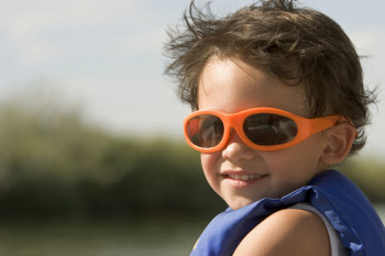 Child wearing sunglasses for eye protection from UV rays