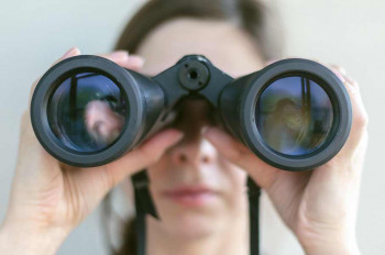 A woman looks through binoculars