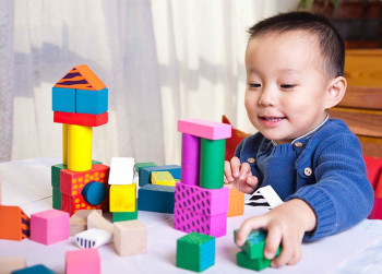 A boy plays with blocks and improves his hand-eye coordination