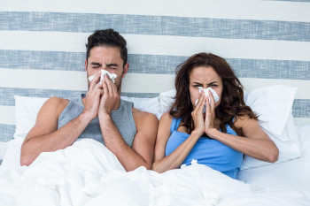 A couple in their bedroom has allergies