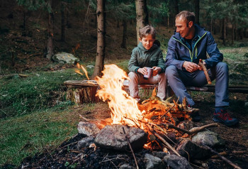 A father and son avoid campfire smoke.