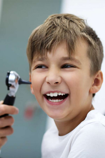A boy has his ear checked for infection.