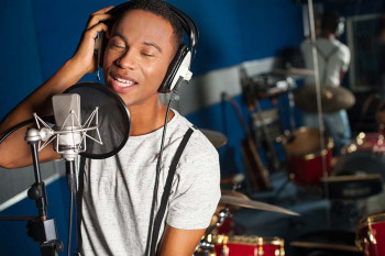 A man listens to himself sing in a recording studio