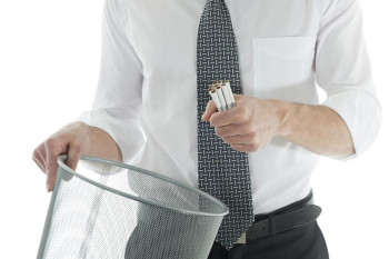A man throws cigarettes in the garbage after quitting smoking