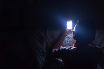 A person uses their phone at night.