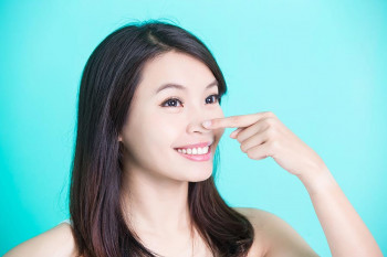 A woman points to her nose after getting a rhinoplasty
