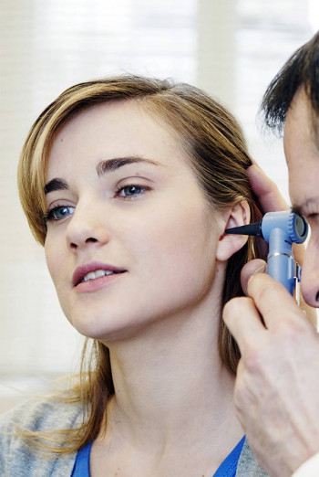 A woman with an adult ear infection gets her ear examined at Charlotte Eye Ear Nose and Throat Associates