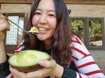 A woman eats an avocado to help with her allergies