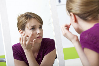 A woman examines her eyes in the mirror