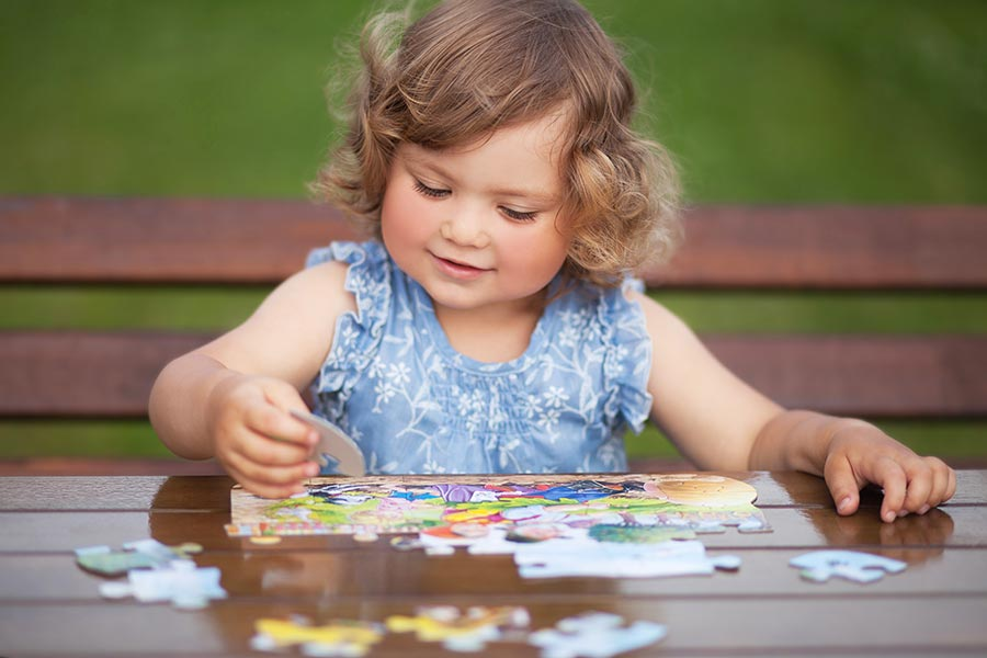 A child plays with a puzzle while improving her hand-eye coordination