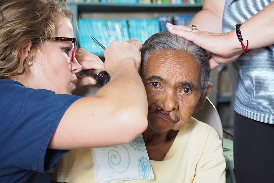Audiologist Molly Koester, AuD, checks a patient's ear