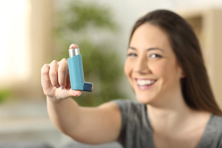 A woman holds up her inhaler, which she uses to treat allergy-related asthma.